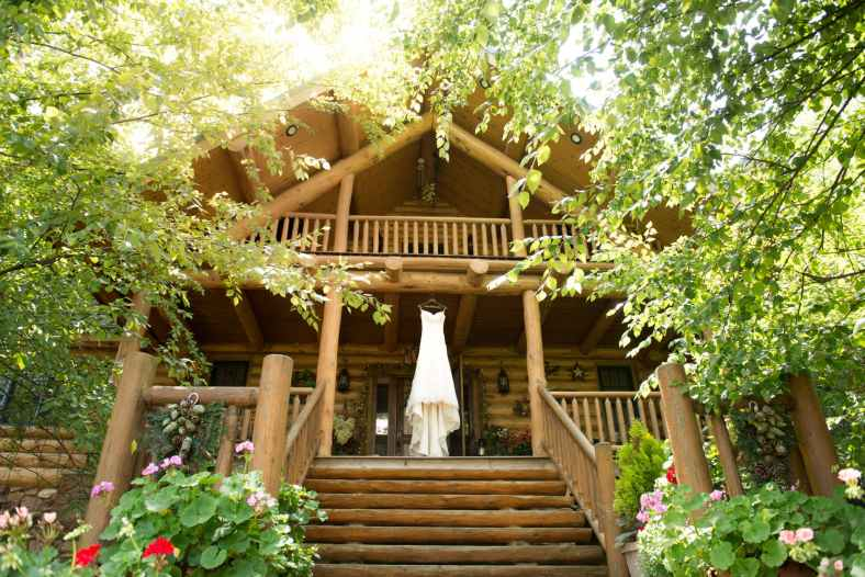 low angle photo of white dress placed on wooden deck surrounded with trees